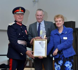 Image of Lord Lieutenant of West Midlands and Beacon Volunteer holding the Queens Award.